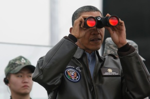 U.S. President Barack Obama looks through a pair of binoculars as he visits the DMZ bordering North from South Korea